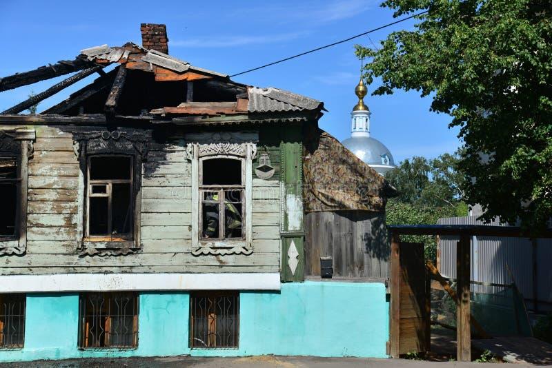 La vecchia casa di legno del villaggio dopo fuoco e la chiesa fotografia stock libera da diritti