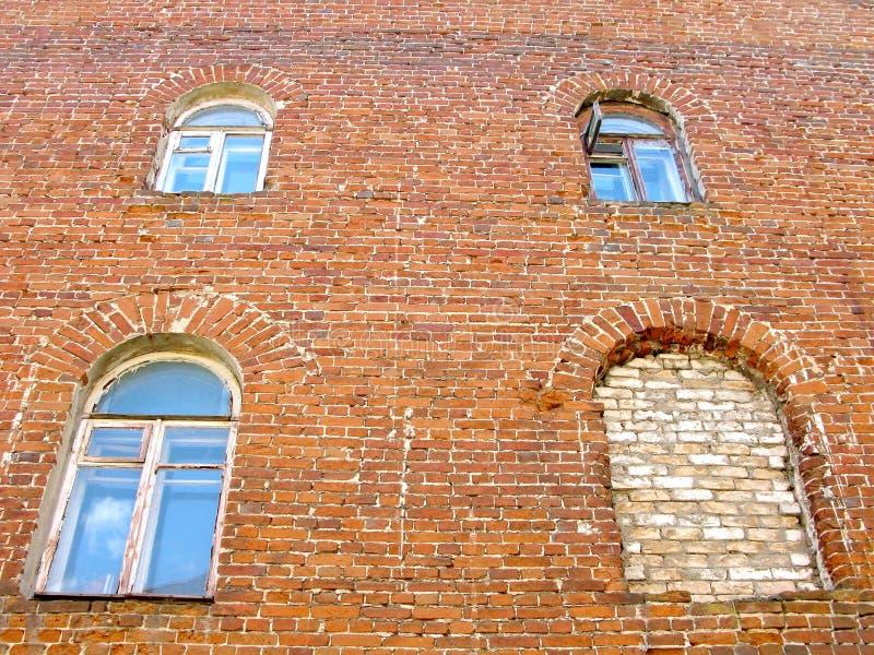 La vecchia casa residenziale, muro di mattoni, ha incurvato le finestre, una bricked sulla finestra immagine stock