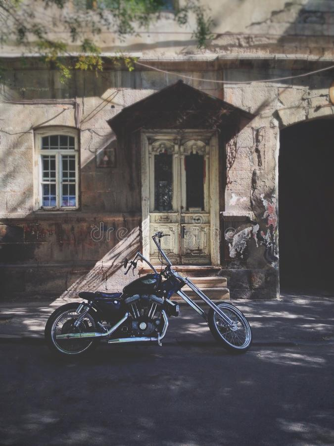 La vecchia costruzione davanti lui è un vecchio motociclo fotografie stock
