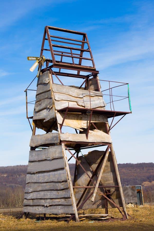 La vecchia costruzione metallica triangolare ha ricoperto i supporti del bordo di legno in montagne sulla foresta del fondo immagini stock