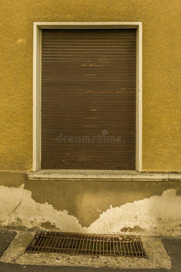 La vecchia facciata con gli otturatori di legno marroni e l'asse per il seminterrato vincono immagini stock