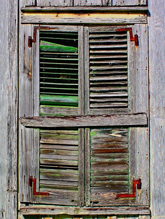 La vecchia, finestra di legno marrone stagionata è coperta di otturatori dilapidati fotografia stock