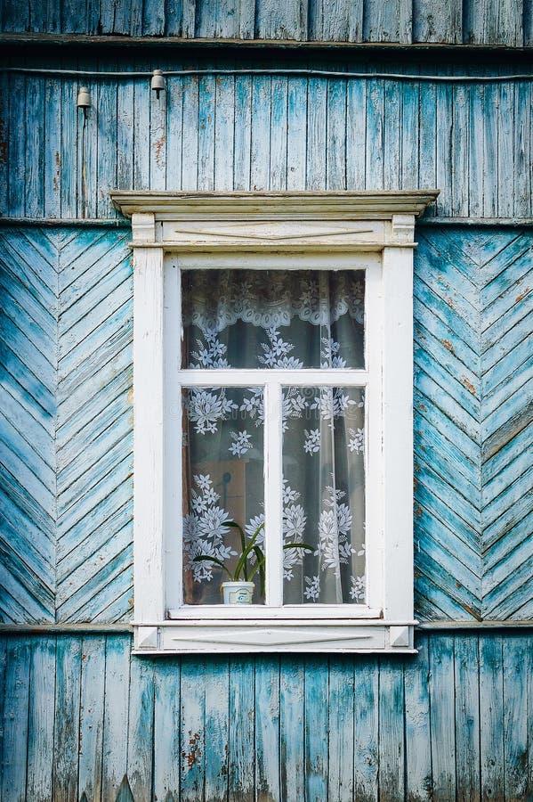 La vecchia finestra di legno stagionata con le cerniere e gli otturatori scolpiti retro fotografia stock
