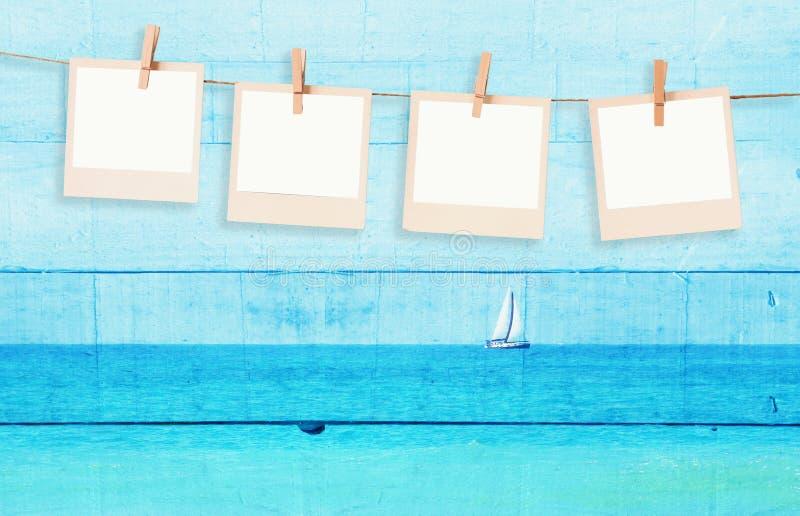 La vecchia foto della polaroid incornicia hnaging su una corda con l'immagine della doppia esposizione della barca a vela all'ori immagine stock