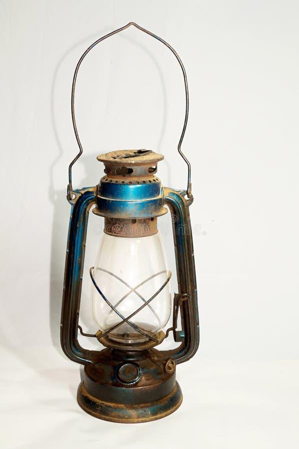 La vecchia lanterna dell'olio è sistemata su una superficie bianca fotografia stock