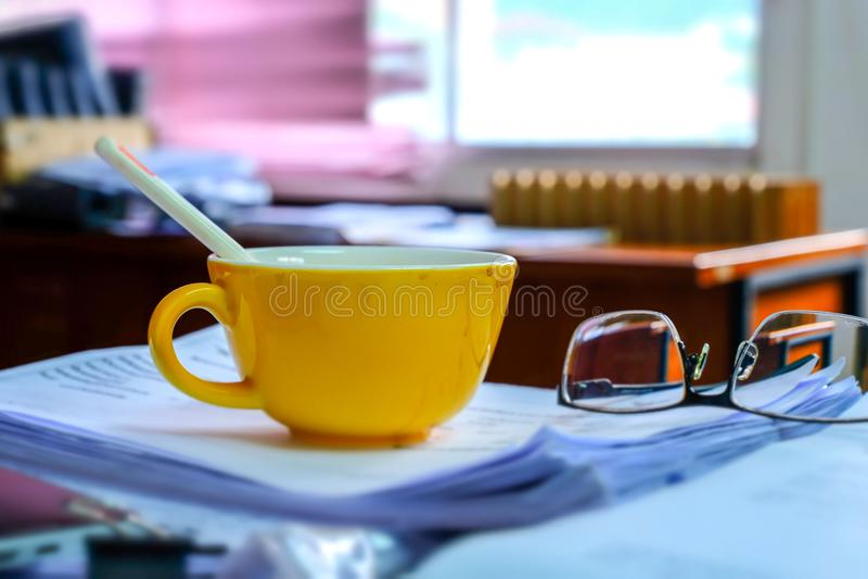 La vecchia macchia gialla del caffè con i vetri ha messo sopra le carte della pila sul immagini stock libere da diritti