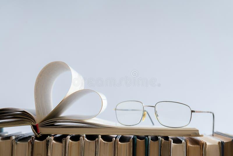 La vecchia pagina del libro della copertina rigida decora a forma del cuore con i vetri sopra immagine stock