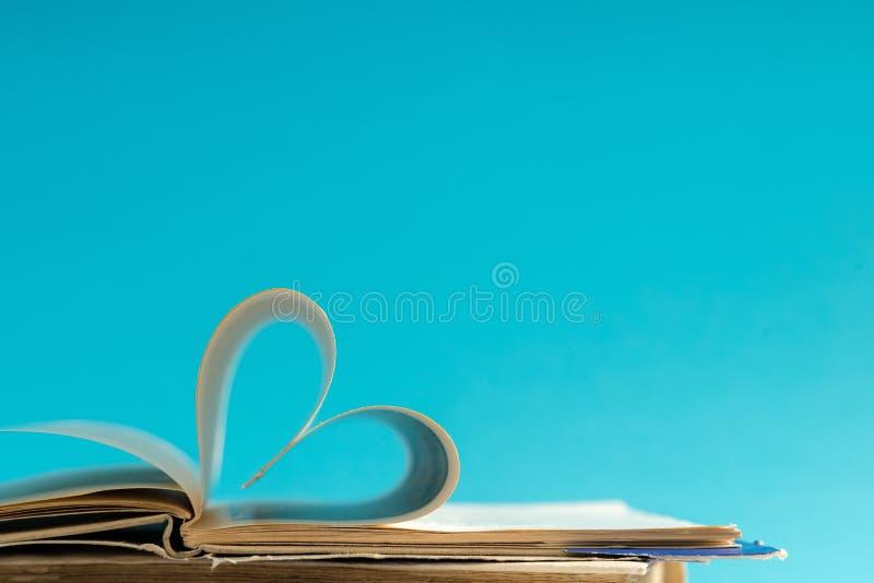 La vecchia pagina del libro della copertina rigida decora a forma del cuore per amore in val immagine stock