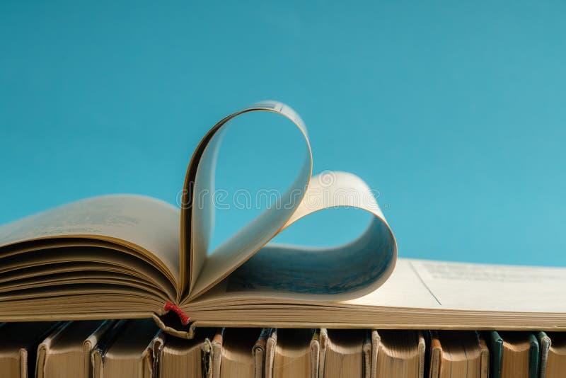 La vecchia pagina del libro della copertina rigida decora a forma del cuore per amore in val immagini stock
