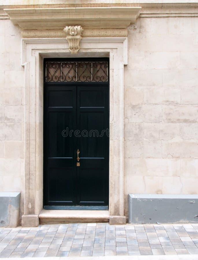 La vecchia porta di legno nera messa in una pietra bianca decorata ha scolpito la struttura e la parete classiche di stile con pa fotografie stock libere da diritti