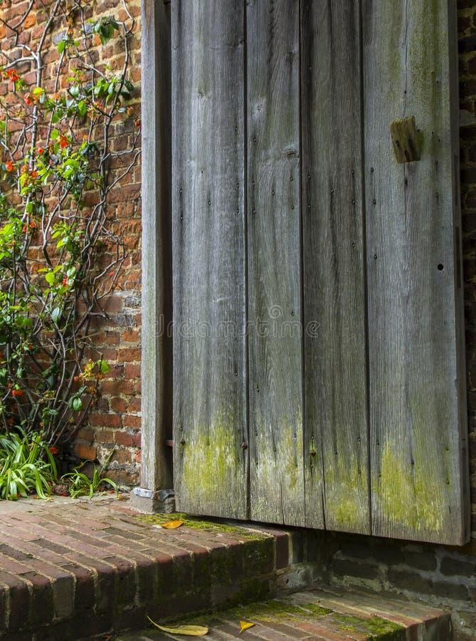 La vecchia porta di legno si apre ad un giardino dimenticato immagini stock
