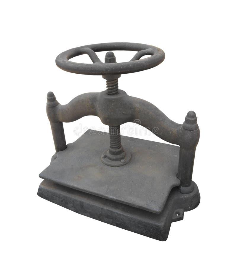 La vecchia rotella del ghisa ha girato la pressa di libro isolata. fotografia stock