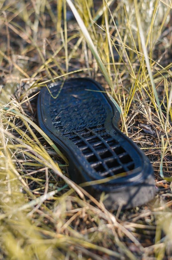 La vecchia scarpa sola si trova sulla terra Bagni dalla pioggia Fuoco molle immagini stock libere da diritti