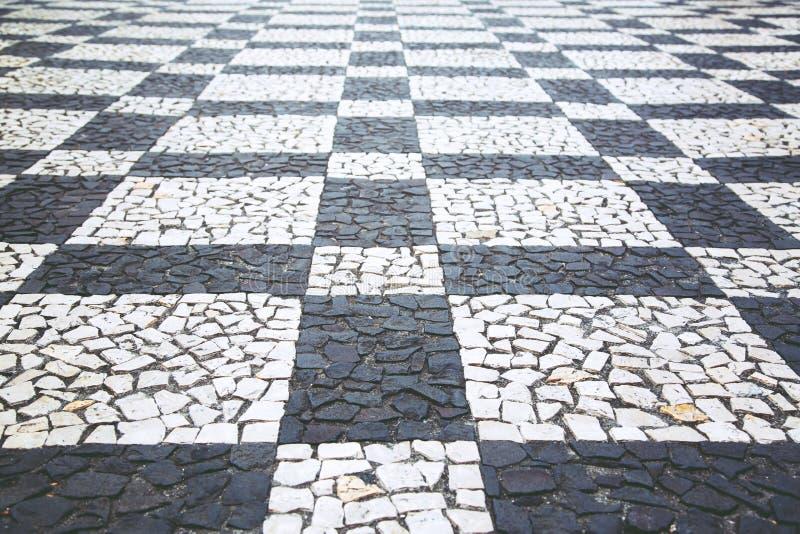 La vecchia strada della via ha pavimentato la scacchiera di pietra di superficie del modello di struttura del passaggio pedonale  fotografia stock