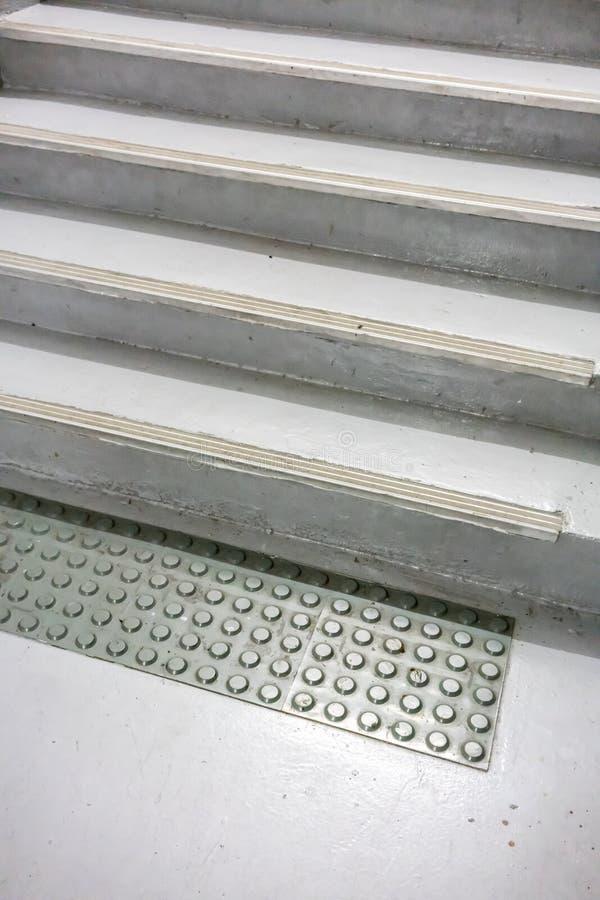 La vecchia stuoia antisdrucciolevole grigia sul pavimento a bianco ha dipinto le scala chiuse fotografie stock libere da diritti