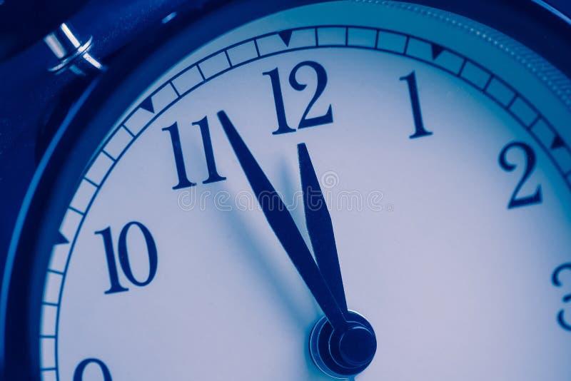 La vecchia sveglia d'annata sta mostrando il movimento di mezzanotte o di mezzogiorno, immagine stock