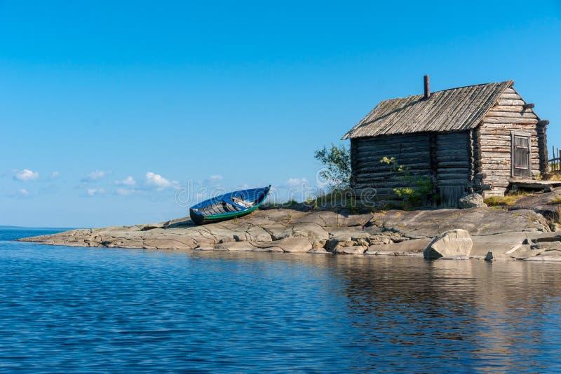 La vecchie capanna e barca di legno sui laghi rocciosi puntellano, la Russia fotografia stock libera da diritti