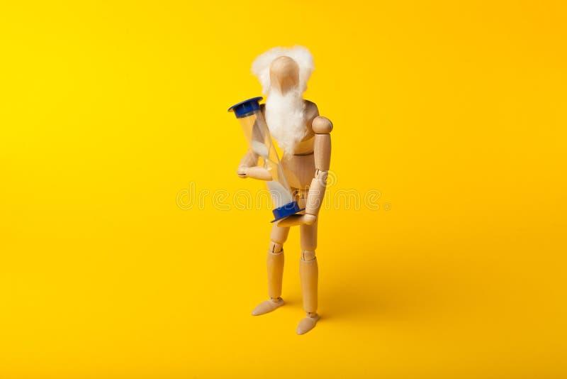 La vejez y el acercamiento a la muerte, la figura de un hombre tiene un reloj de arena en el que el tiempo se acaba fotografía de archivo