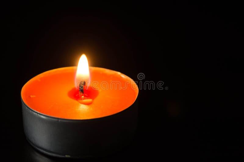 La vela ardiente contra un fondo oscuro imagenes de archivo