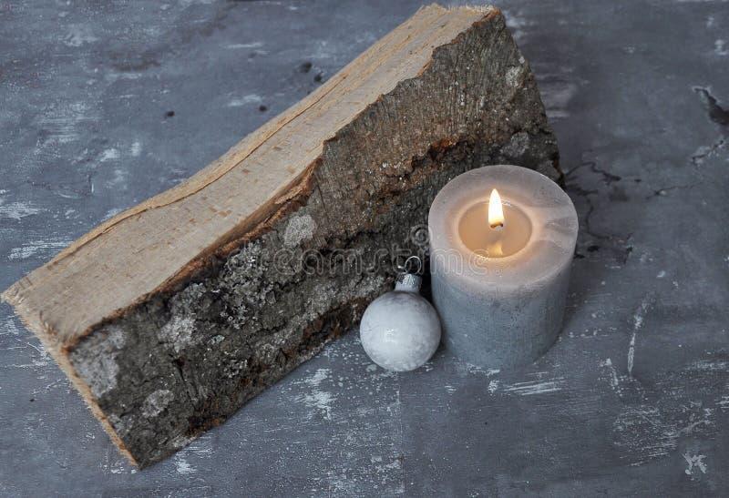 La vela, la chuchería del árbol de navidad y la madera ardientes alojan en el hormigón foto de archivo