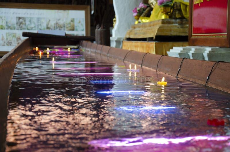 La vela colorida de rogación ritual que flota en el agua para ruega la imagen de descanso de Buda en Wat Phra Non Chakkrasi Woraw foto de archivo libre de regalías