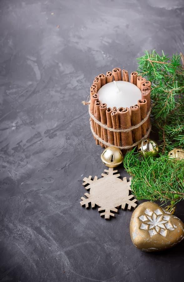 La vela con canela, la decoración de la Navidad y el enebro ramifican en fondo oscuro foto de archivo libre de regalías