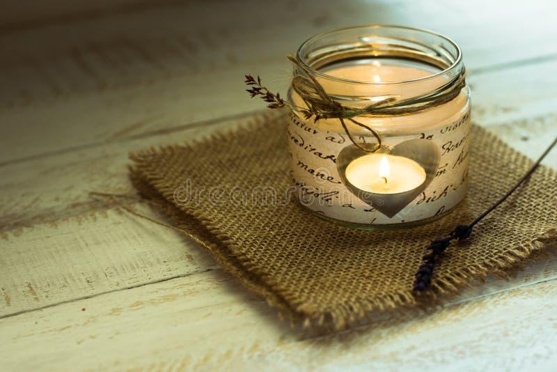 La vela en forma de corazón en tarro con guita y el campo delicado florecen, tarjeta del día de San Valentín, casandose la decora foto de archivo