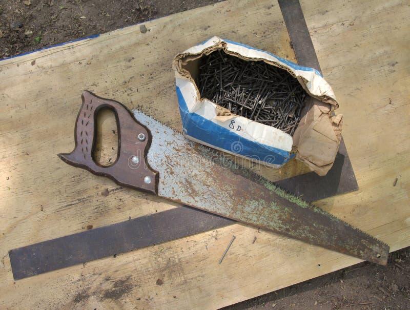 La vendimia vio, los clavos y el cuadrado del carpintero fotos de archivo