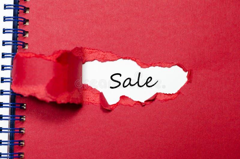 La vendita di parola che compare dietro la carta lacerata immagini stock