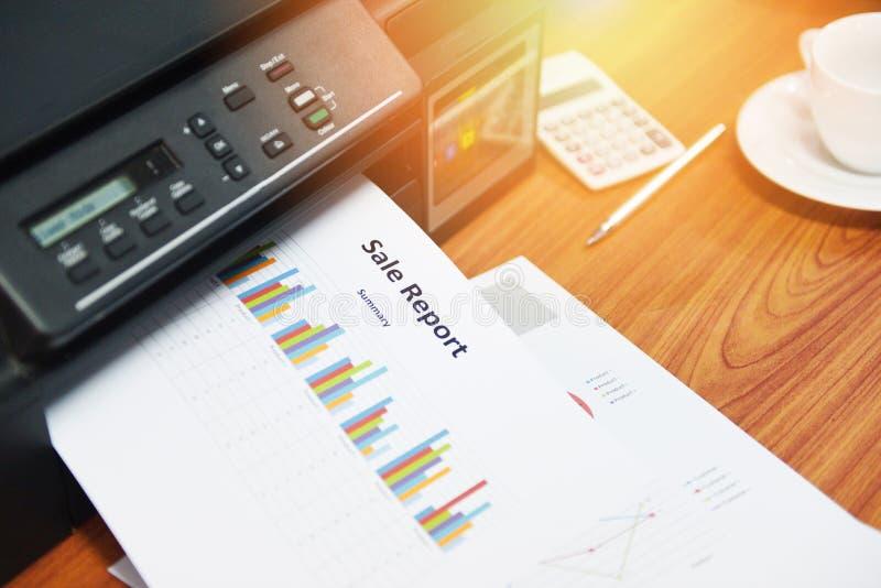 La venta de los informes de negocios de la impresión de la impresora y la pila de documentos divulgan la carta del gráfico en la  foto de archivo