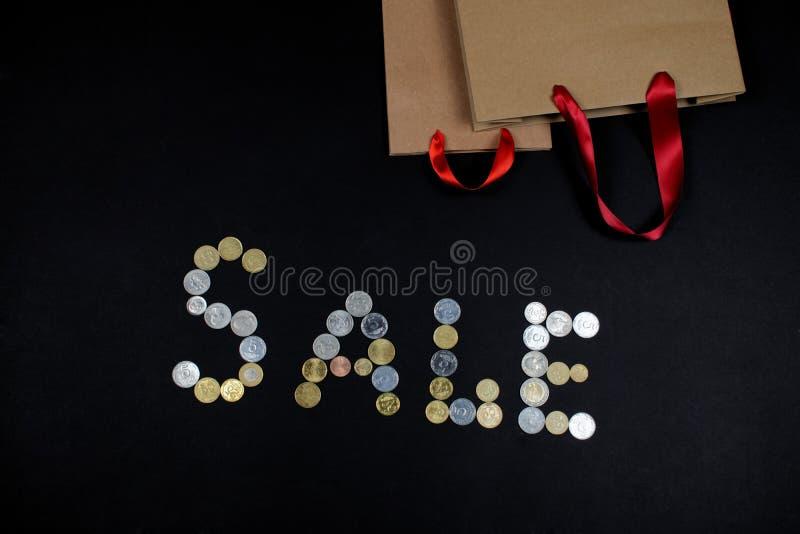 La venta de la palabra escrita con las monedas y dos bolsas de papel fotos de archivo libres de regalías