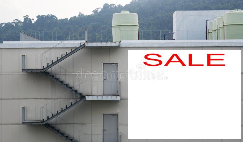 La venta Real Estate firma delante de salida de incendios y de tubería de la escalera imagenes de archivo
