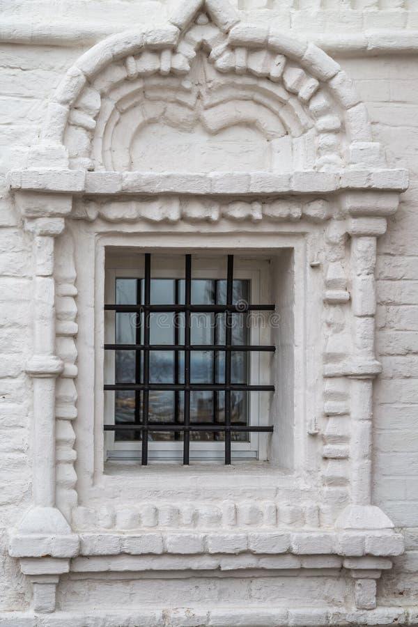 La ventana con las barras en la iglesia ortodoxa del blanco lavó el ladrillo Espacio para insertar el texto imagen de archivo libre de regalías