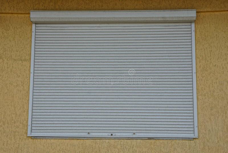 La ventana cuadrada se cerró por la persiana gris en una pared fotos de archivo libres de regalías