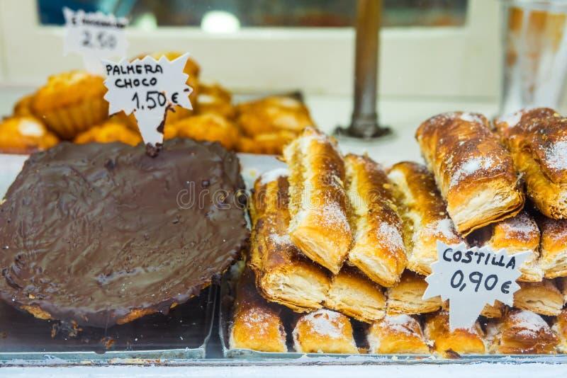 La ventana de exhibición de una panadería del artesano en ciudad española en Costa Blanca, dulces de la pasta de hojaldre, chocol fotografía de archivo