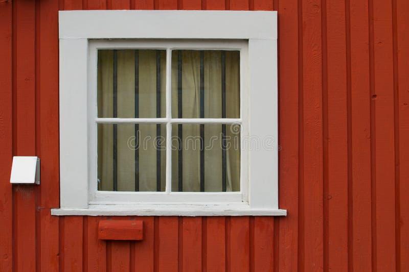 La ventana de la casilla blanca fijó en una pared de madera roja foto de archivo