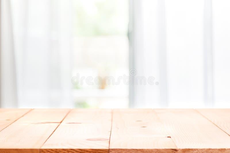 La ventana Defocused de la cortina y vacia de la sobremesa de madera con luz del sol caliente imagenes de archivo