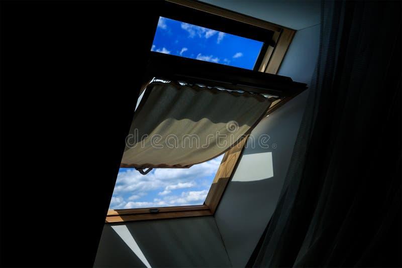 La ventana del ático oscuro, abierta Una vista de un cielo azul claro con las nubes imagenes de archivo