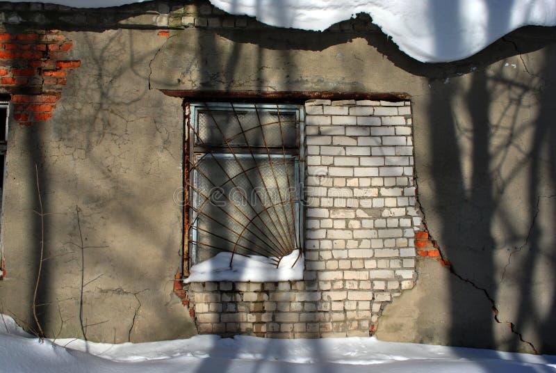 La ventana del edificio de ladrillo viejo en el yeso agrietado cubierto con la rejilla oxidada del hierro, sombras de árboles en  fotos de archivo