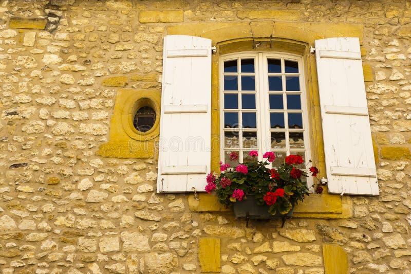 La ventana florece la fachada de piedra Monpazier imágenes de archivo libres de regalías