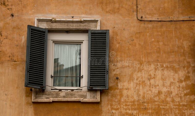 La ventana vieja fijó en una pared vieja, ocre fotos de archivo