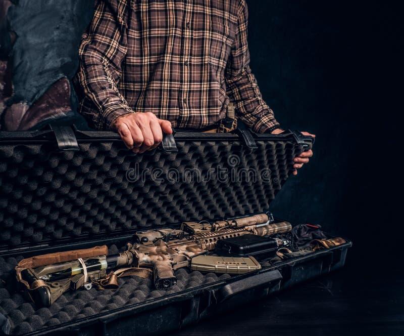 La vente illégale des armes, marché noir, le criminel ouvre la valise avec un fusil d'assaut et la montre à l'acheteur photographie stock libre de droits