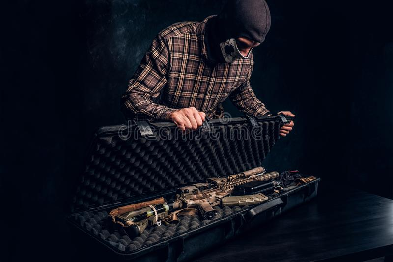 La vente ill?gale des armes, march? noir, le criminel ouvre la valise avec un fusil d'assaut et la montre ? l'acheteur images stock