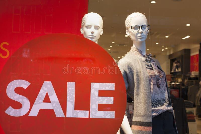 La vente se connectent des poupées de fenêtre et de mode de boutique dans le magasin photos stock