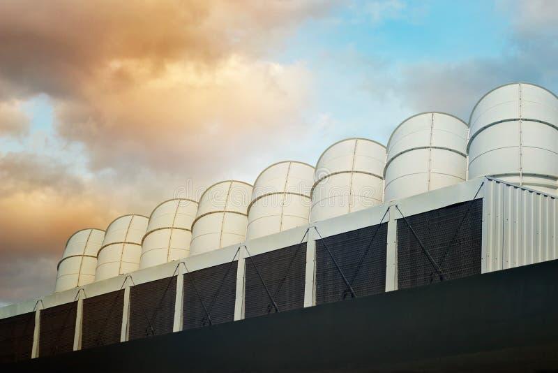 La ventilación instala tubos en el tejado de un edificio industrial en fondo colorido del cielo imagen de archivo