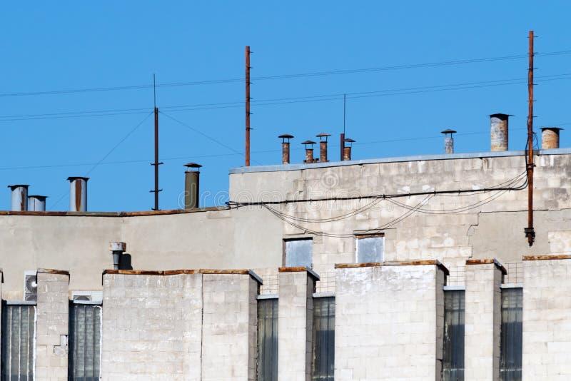 La ventilación instala tubos en el tejado del edificio de varios pisos contra el cielo imagen de archivo
