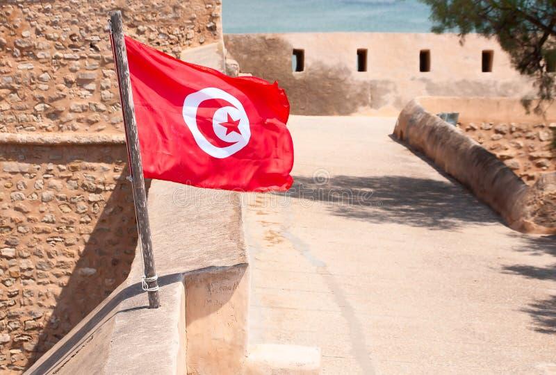 La vera bandiera tunisina contro il muro della fortezza di medina immagine stock