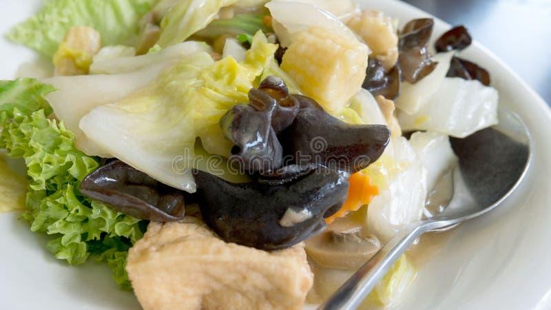 La verdura mista ha soffritto sul piatto bianco sopra il fondo nero della tavola immagini stock libere da diritti