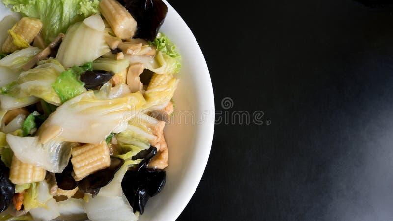 La verdura mista stire-ha fritto sul piatto bianco sopra il fondo nero della tavola fotografia stock libera da diritti