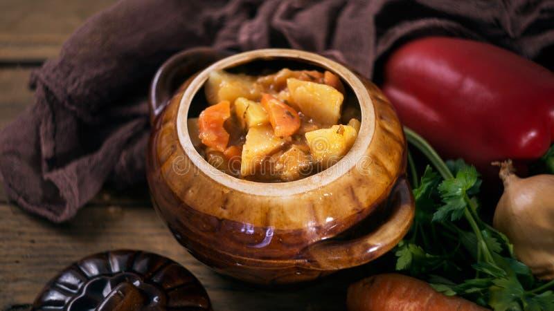 La verdura y la carne guisan en cántaro con las verduras frescas crudas imagen de archivo libre de regalías